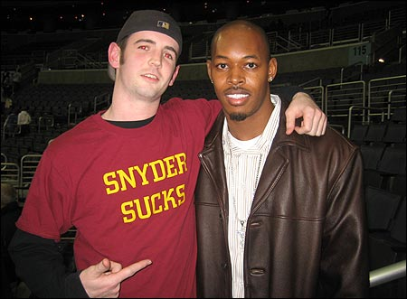 Carlos Rogers poses with a disgruntled Redskins fan. The drama in D.C. continues as owner Dan Snyder recently stripped HC Jim Zorn of his play calling duties.