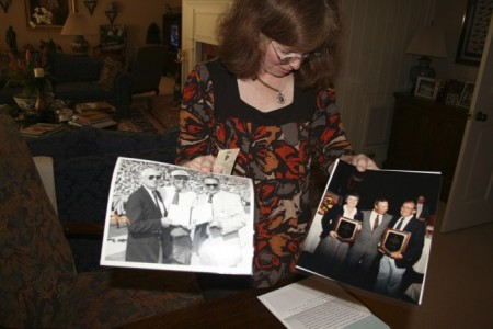 Nancy Teel holds photos of her parents Paul Conner and Dixie Conner receiving distiguised service awards from former Auburn coach Pat Dye, and her father posing with former Auburn University president Dr. William Muse.