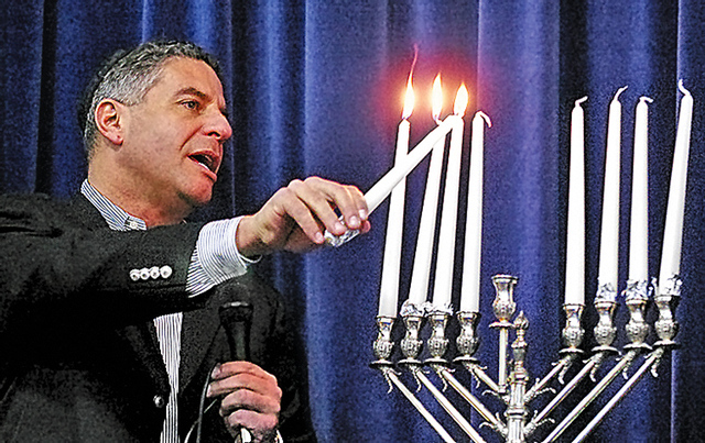 Tuesday,December 11,2007 The University of Tennessee men's basketball coach Bruce Pearl lights the candles of a Hanukkah Menorah during Menorah Madness, an event held at the Arnstein Jewish Community Center that is sponsored by the Knoxville Jewish Alliance and Chabad of Knoxville. The event marks the final day of Hannukah. Saul Young/News Sentinel
